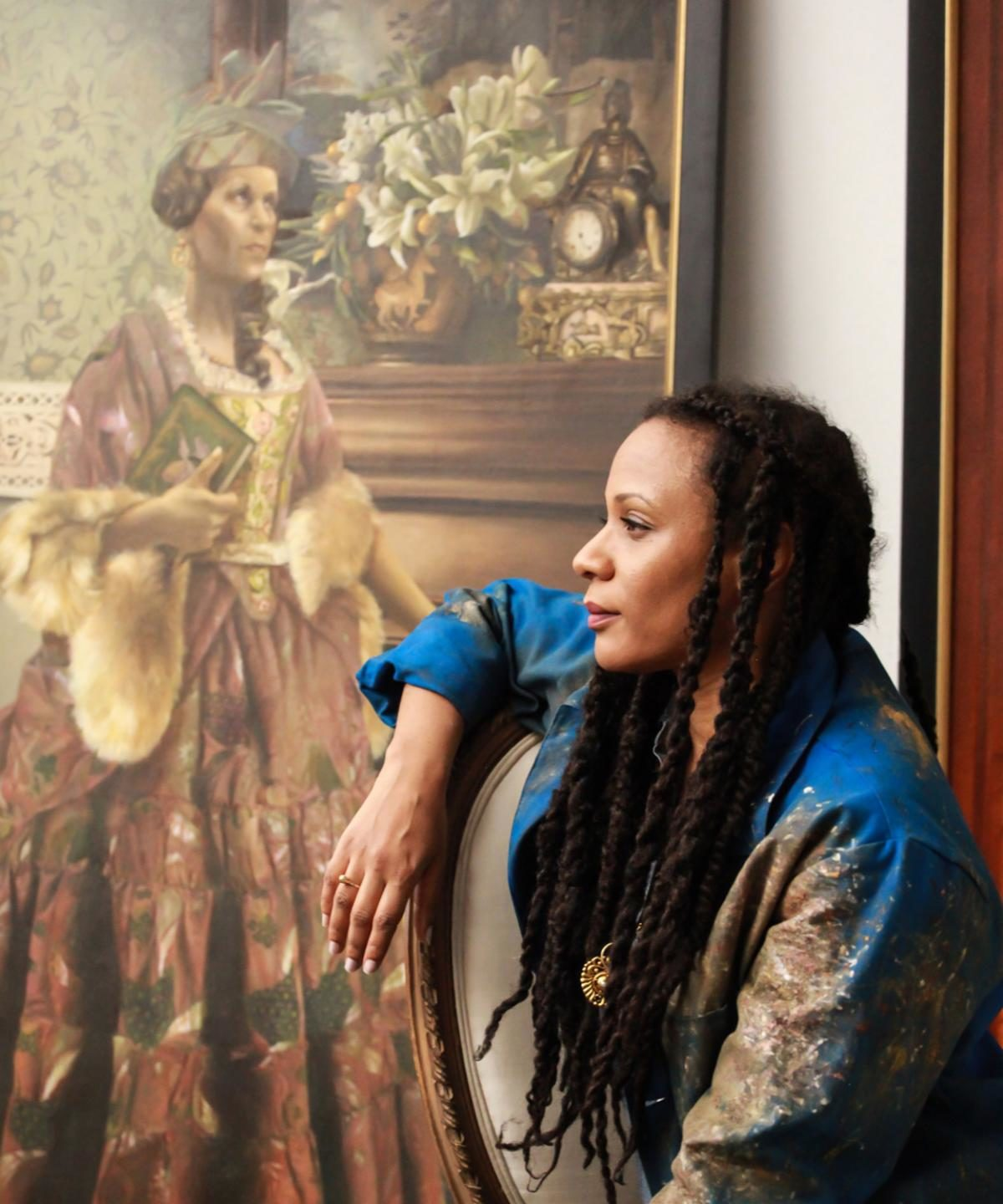 An image of Elizabeth Colomba standing next to a painting.